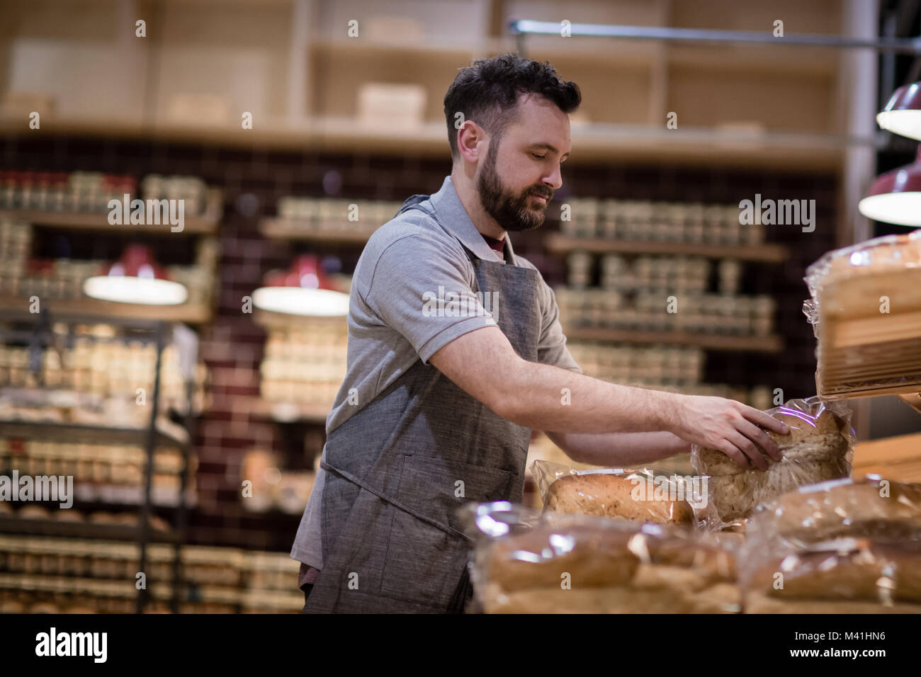Baker in bakery stocking shelves and looking to camera - Stock Image