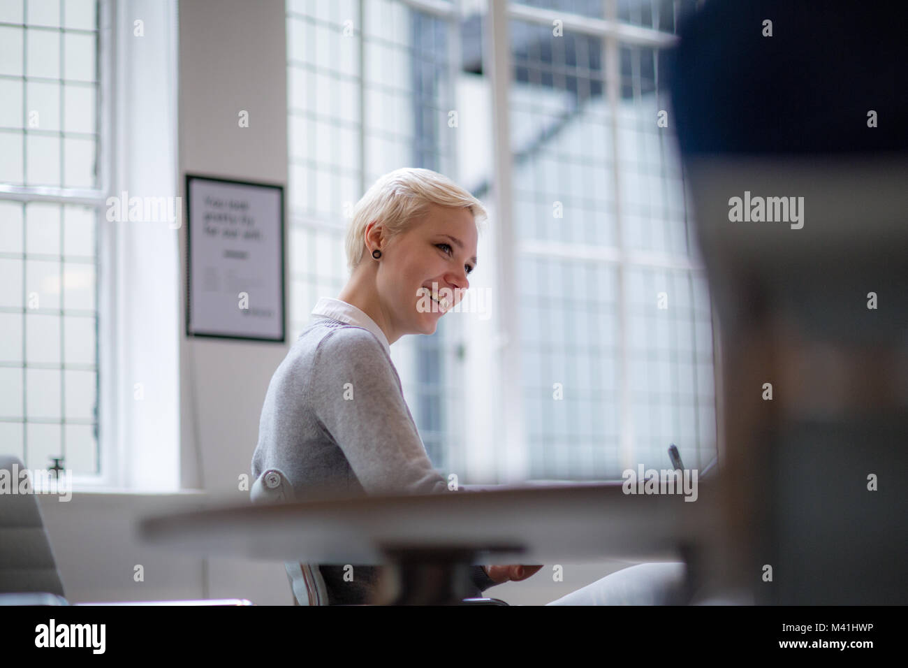 Young female businesswoman taking notes in meeting - Stock Image