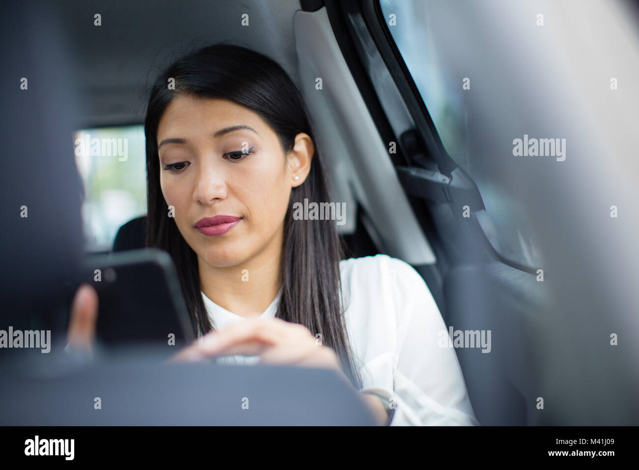 Businesswoman in taxi cab using smartphone - Stock Image