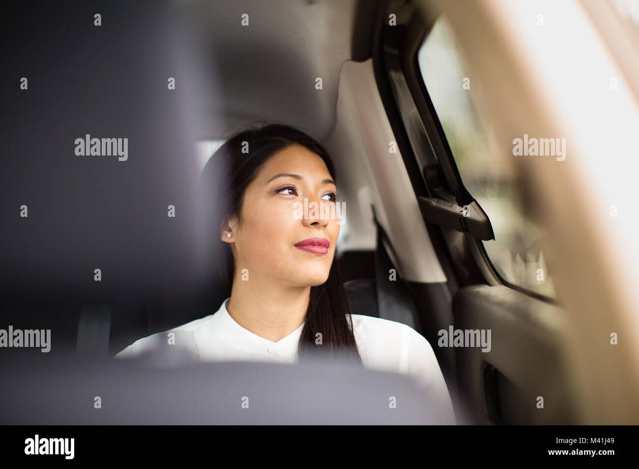 Businesswoman looking out of window of taxi cab - Stock Image