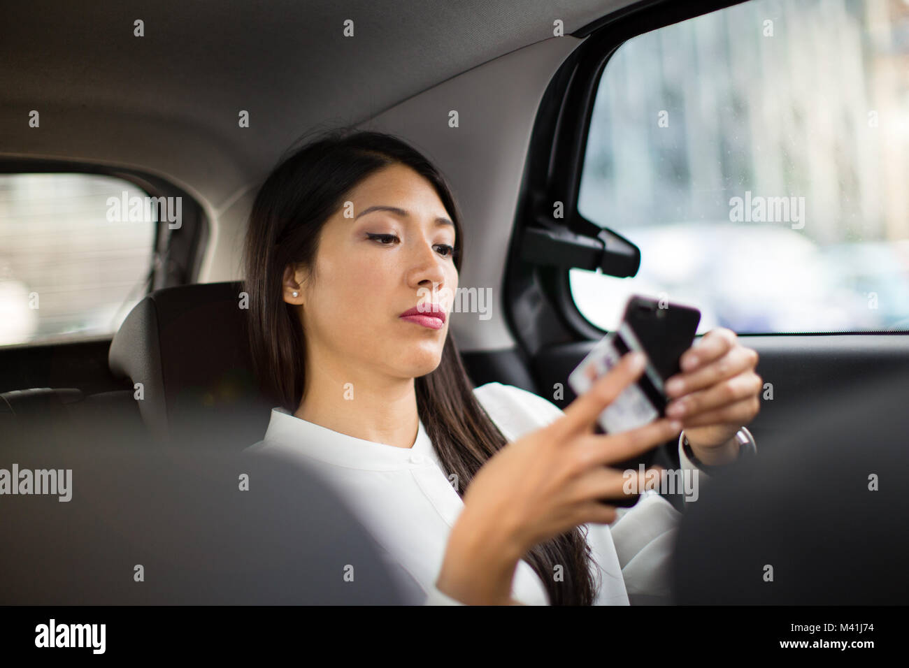 Businesswoman paying via app for taxi cab ride - Stock Image