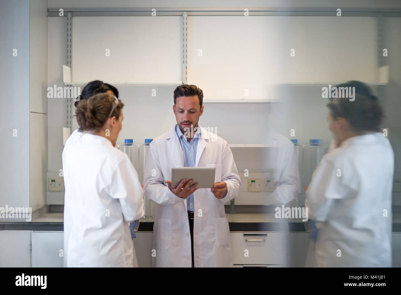 Team of scientists discussing experiment data on digital tablet - Stock Image