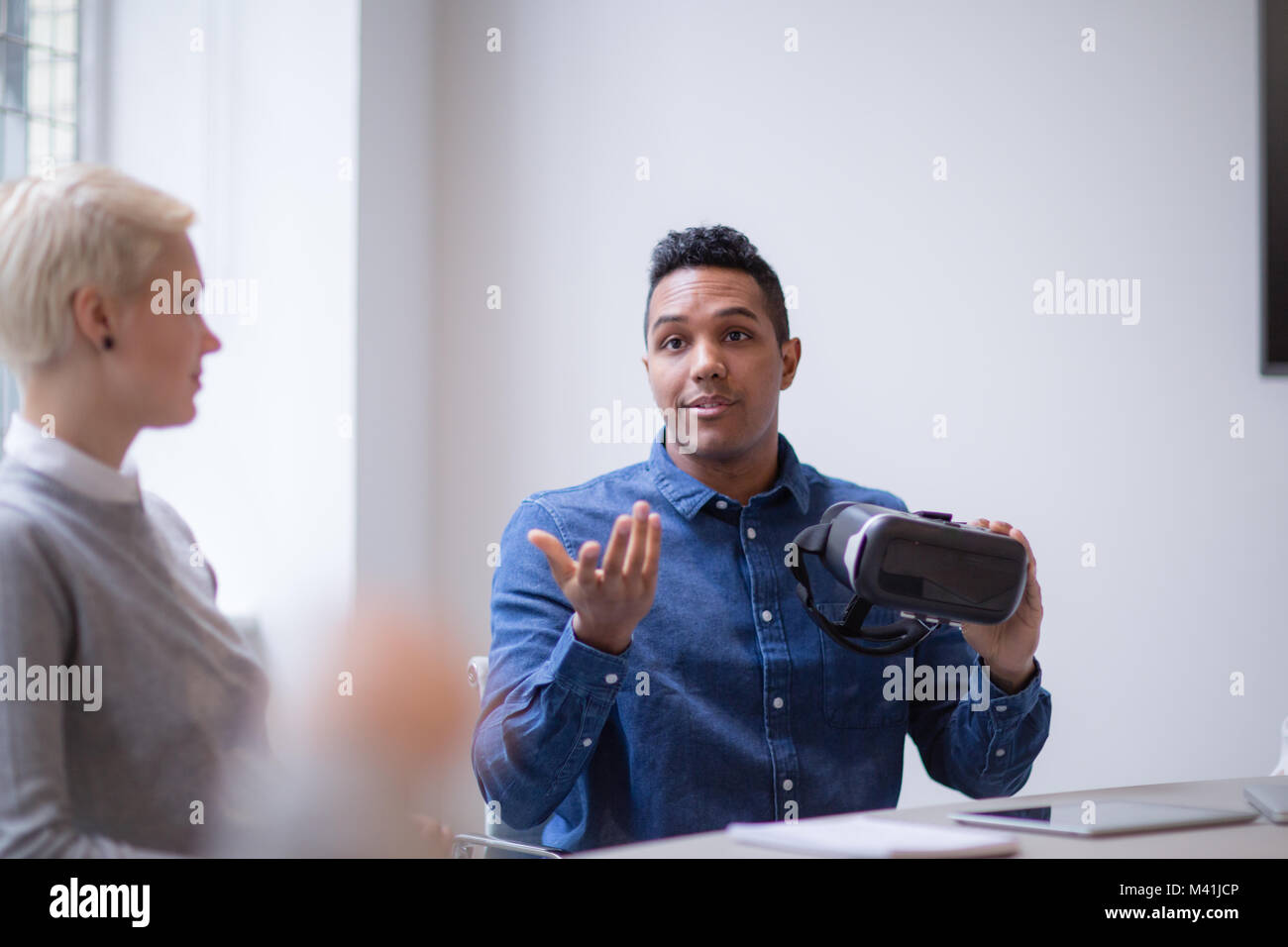 Designer presenting virtual reality headset in a meeting - Stock Image
