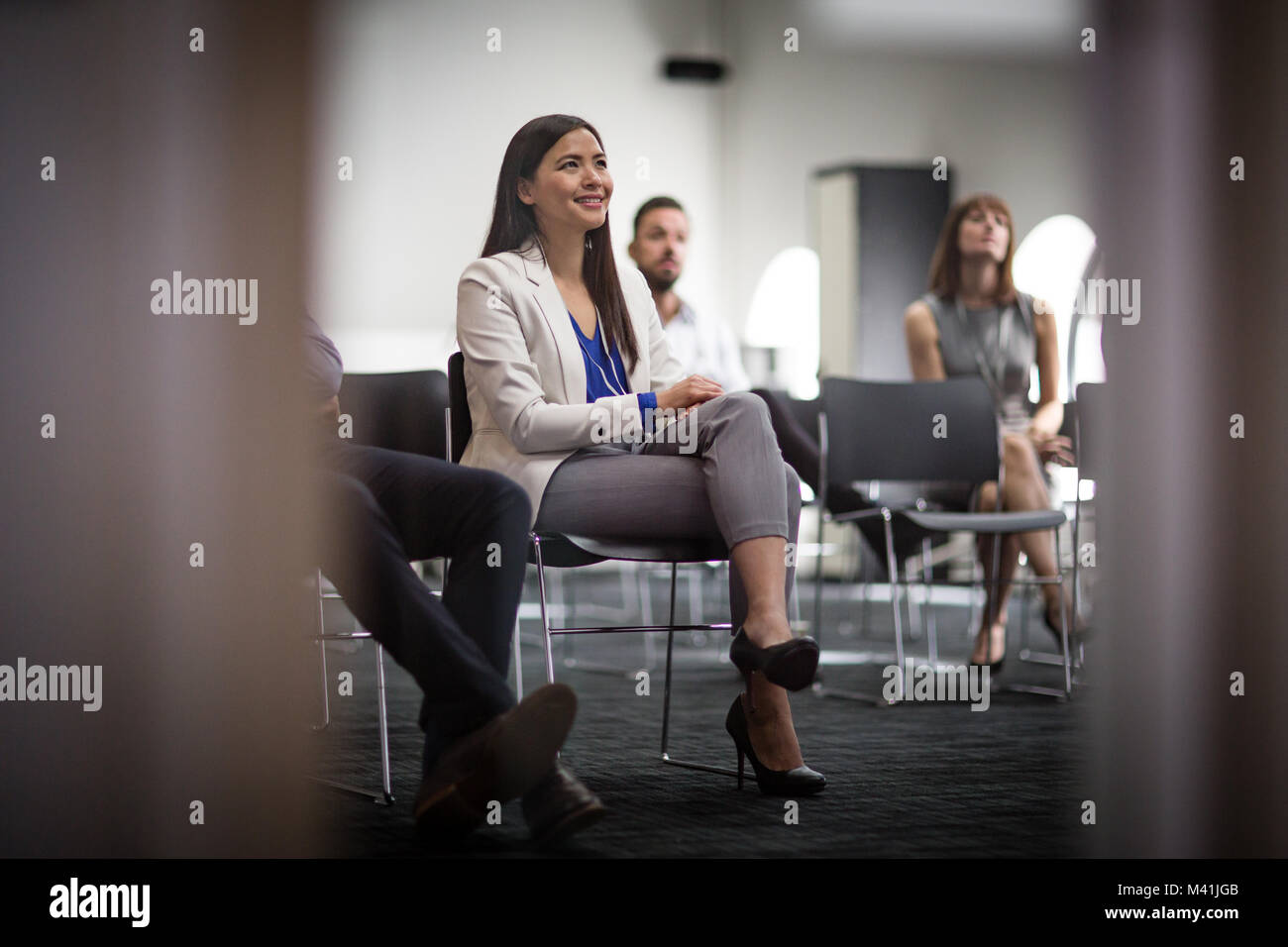 Female executive listening at a business conference - Stock Image
