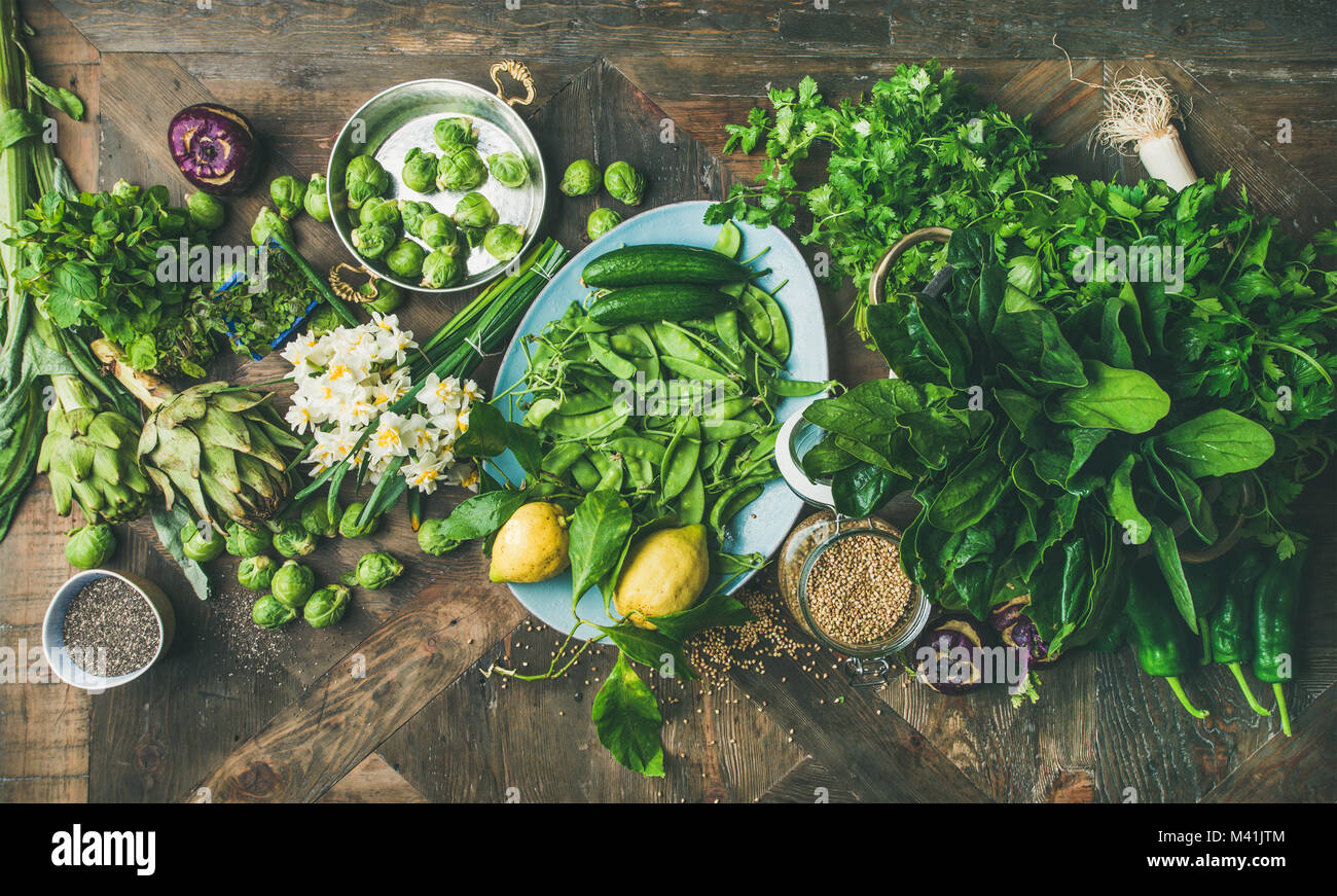 Spring healthy vegan food cooking ingredients, wooden background, top view - Stock Image