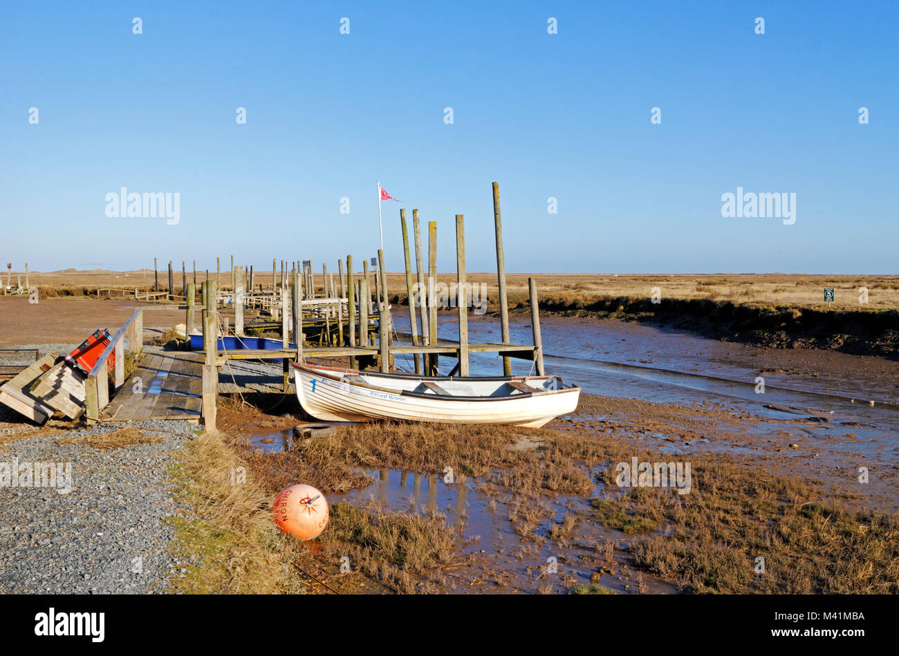 A view of quay heading and small boat in a North Norfolk creek at Morston, Norfolk, England, United Kingdom, Europe. - Stock Image