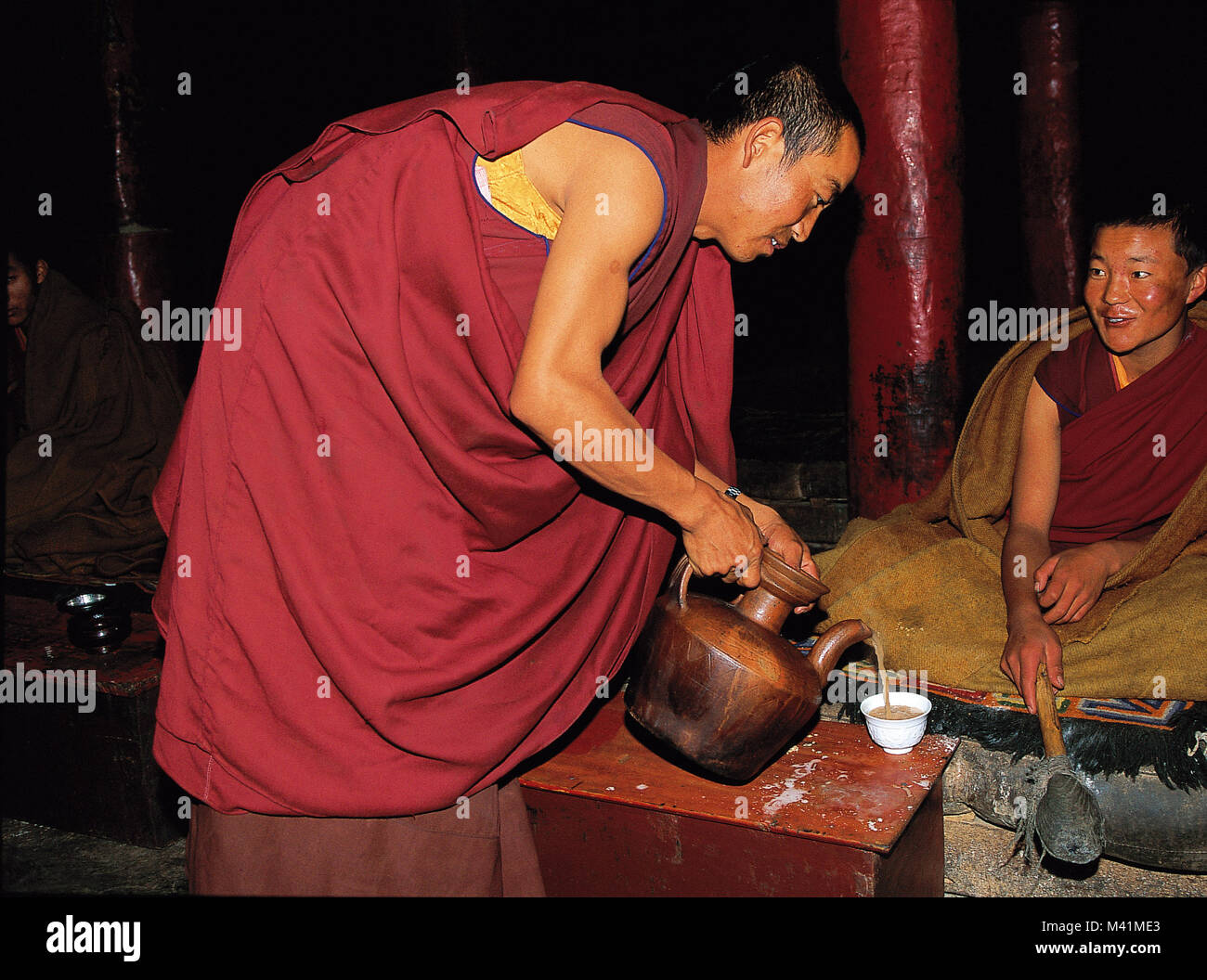 China, Central Tibet, monk serving tea in a monastery, ceremony being a part of the evening gatherings and prayers - Stock Image