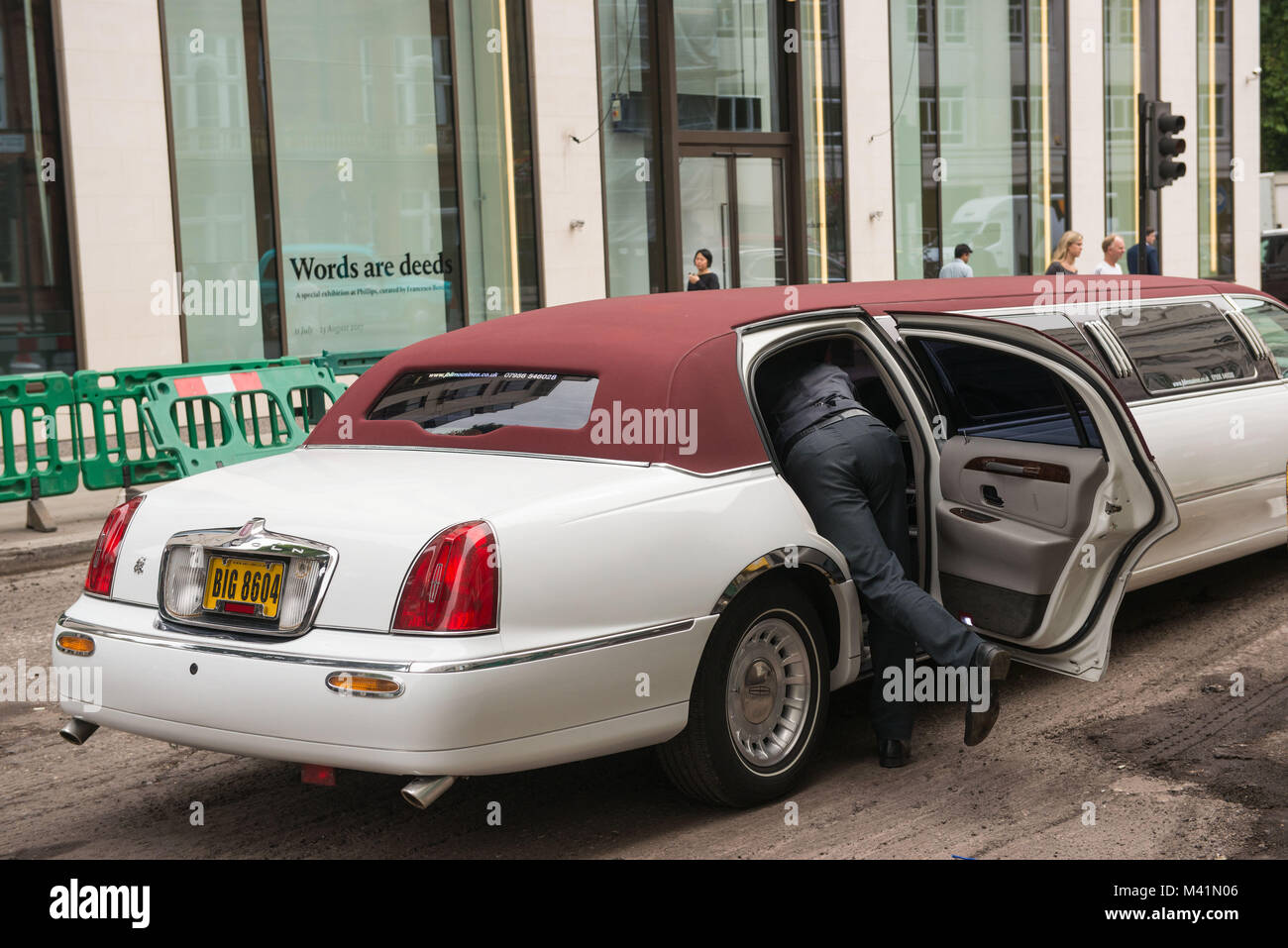 London, United Kingdom.  Driver of a luxury car, Mayfar. - Stock Image