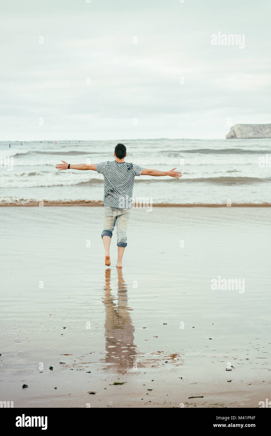 Young man enjoying the day in the beach - Stock Image