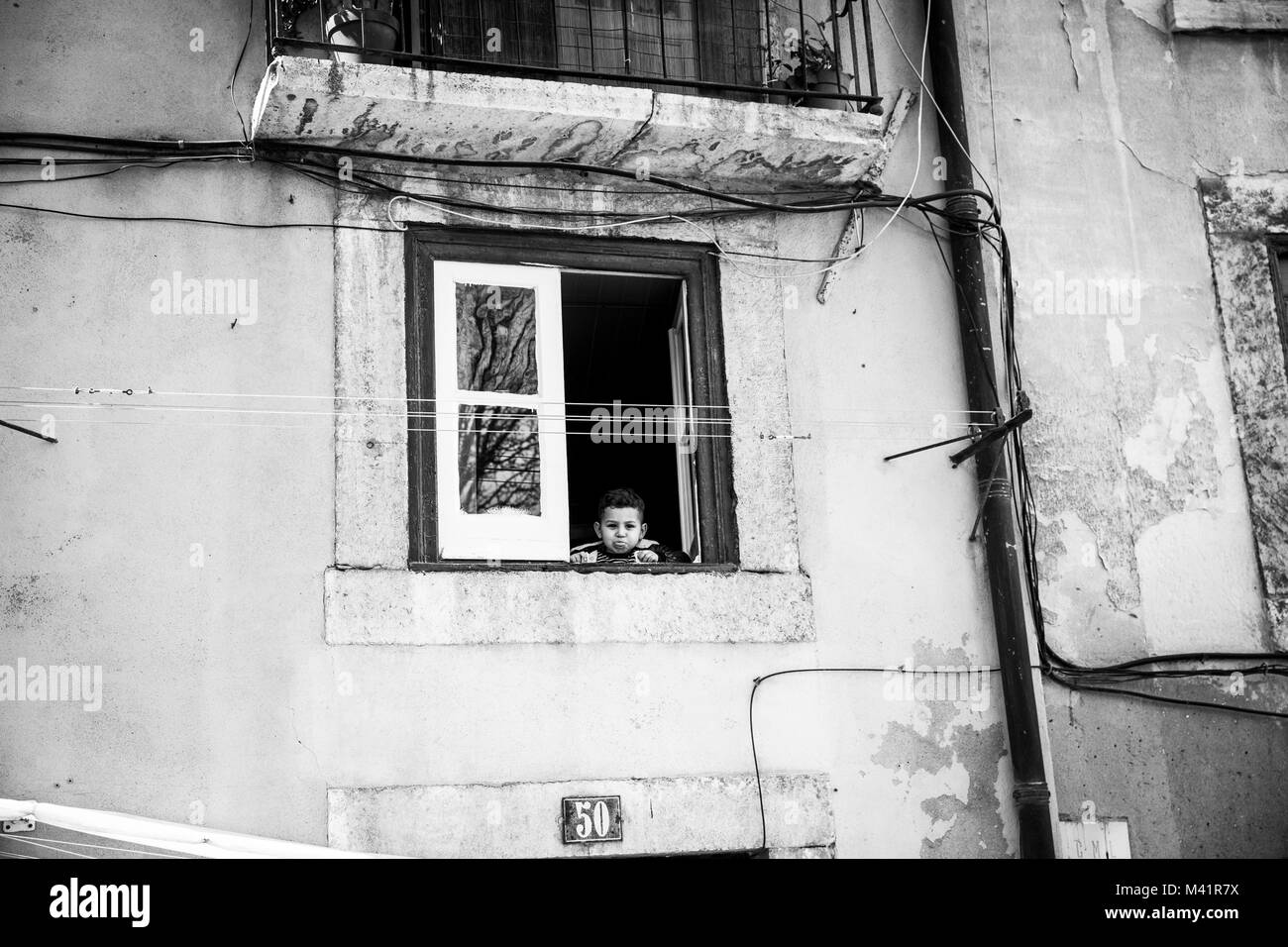 A boy at a window in Lisbon, Portugal. - Stock Image