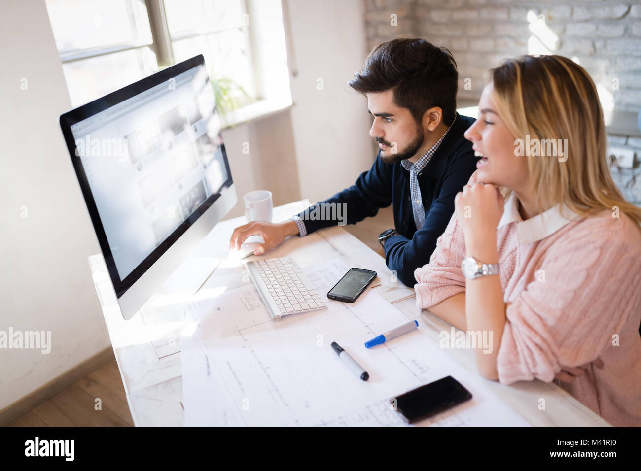 Picture of young architects discussing in office - Stock Image