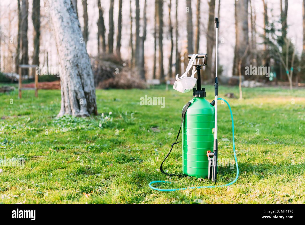 Green sprayer on spring garden - Stock Image