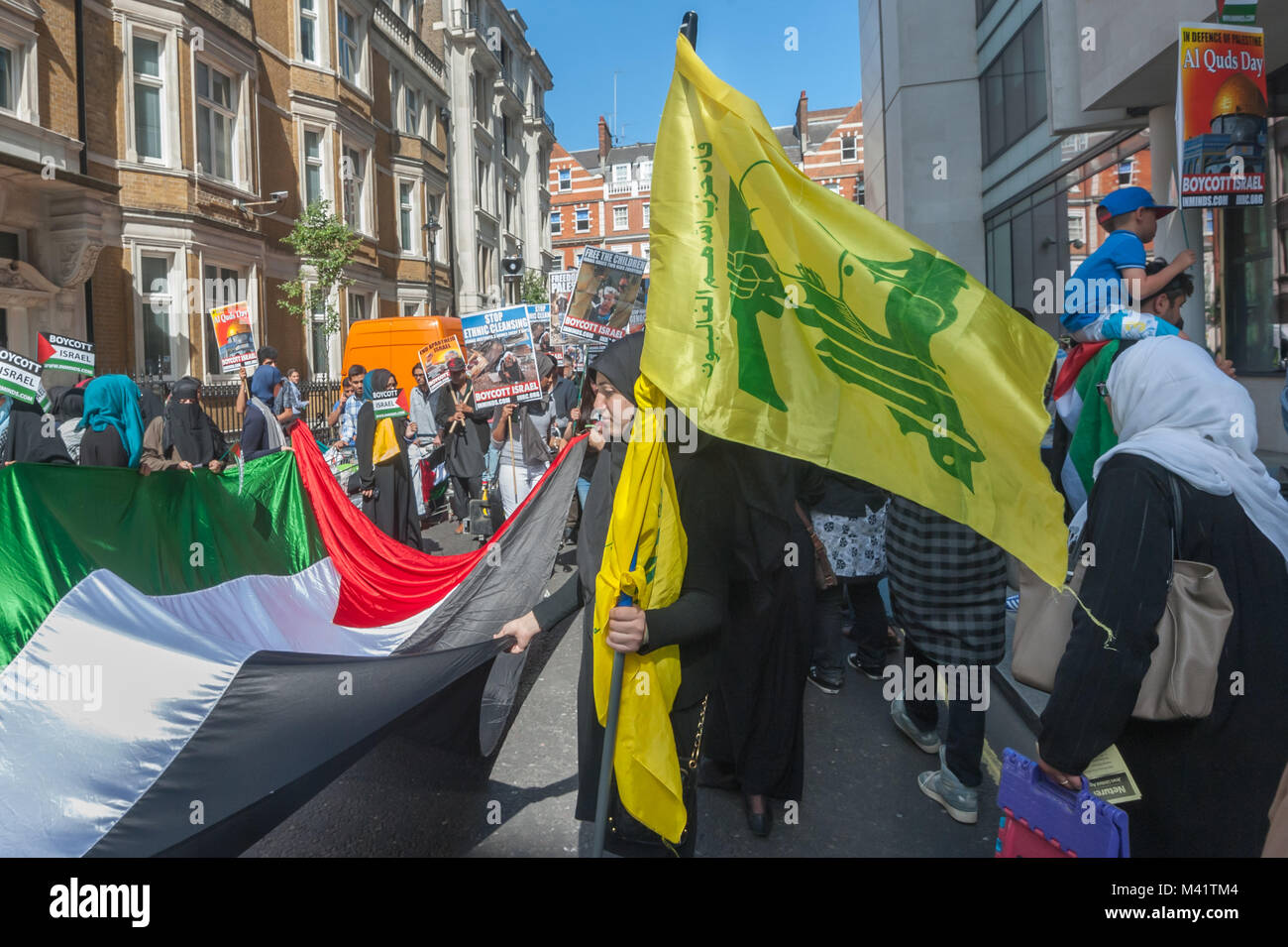 A few people on the march carried green and yellow Hezbollah flags at the Al Quds Day march in London. - Stock Image