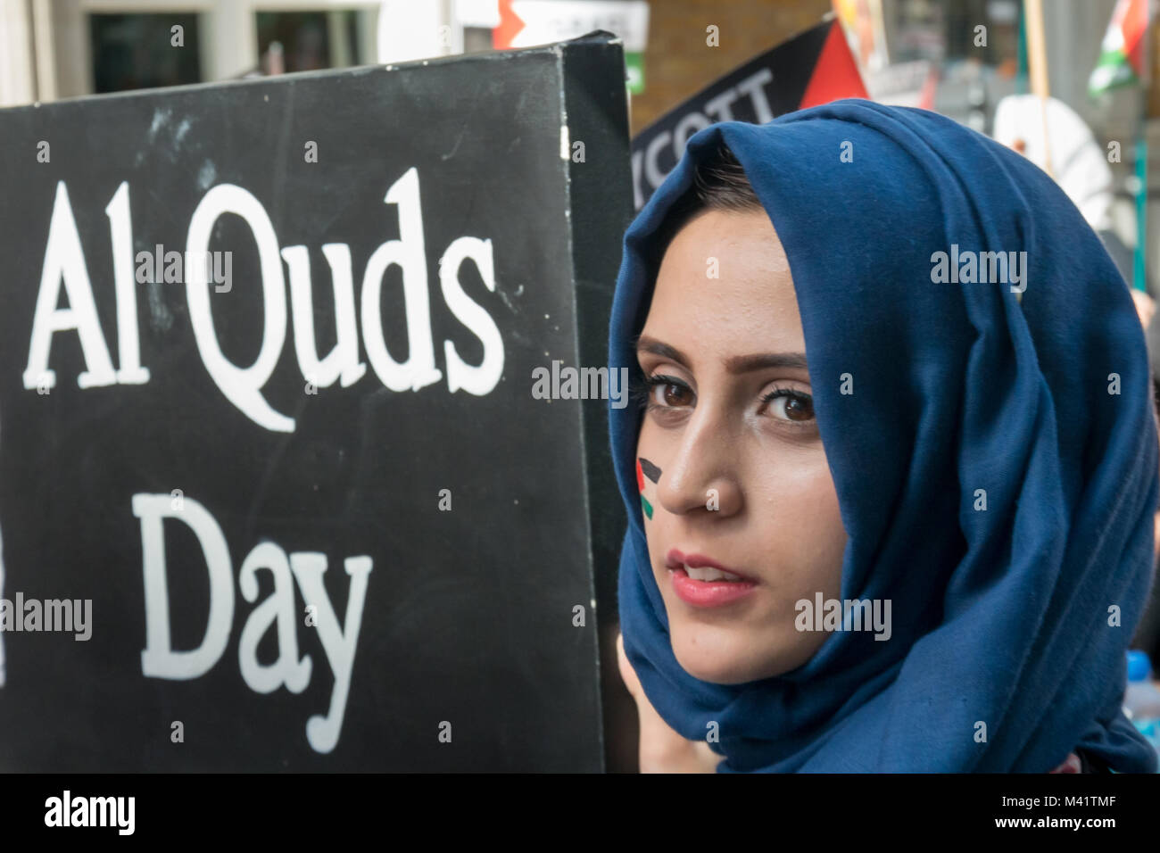 A woman in a blue headscarf with a Palestinian flag painted on her cheek  holds a large board with a message about - Stock Image