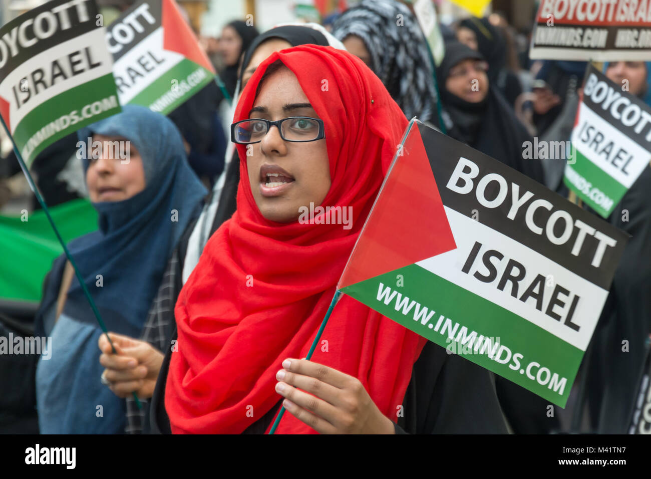 A woman in a red headscarf carries a 'Boycott Israel' Palestinian flag on the Al Quds Day march in London. - Stock Image
