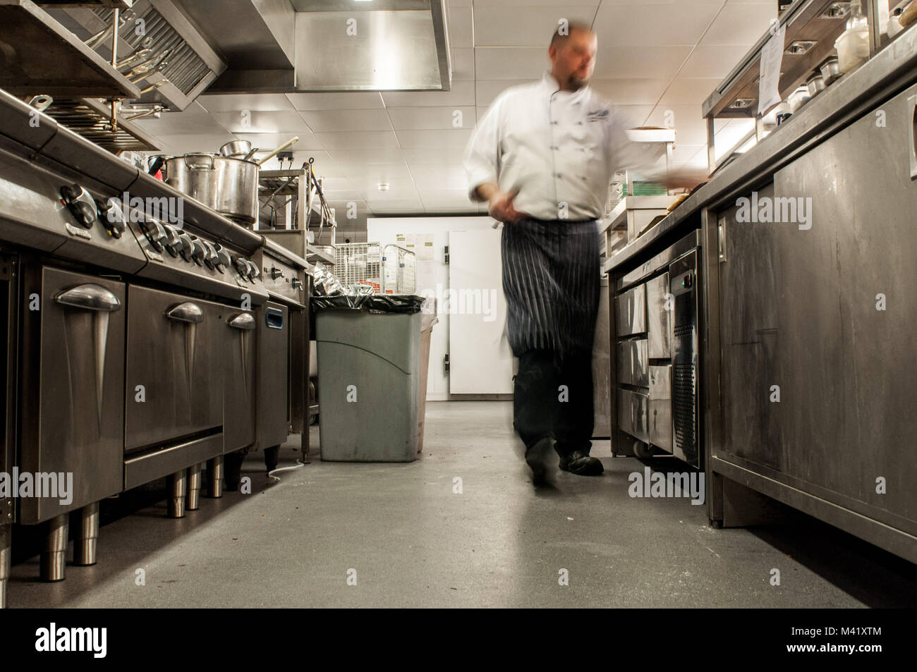 A photo with motion blur of a chef moving quickly in a restaurant kitchen - Stock Image