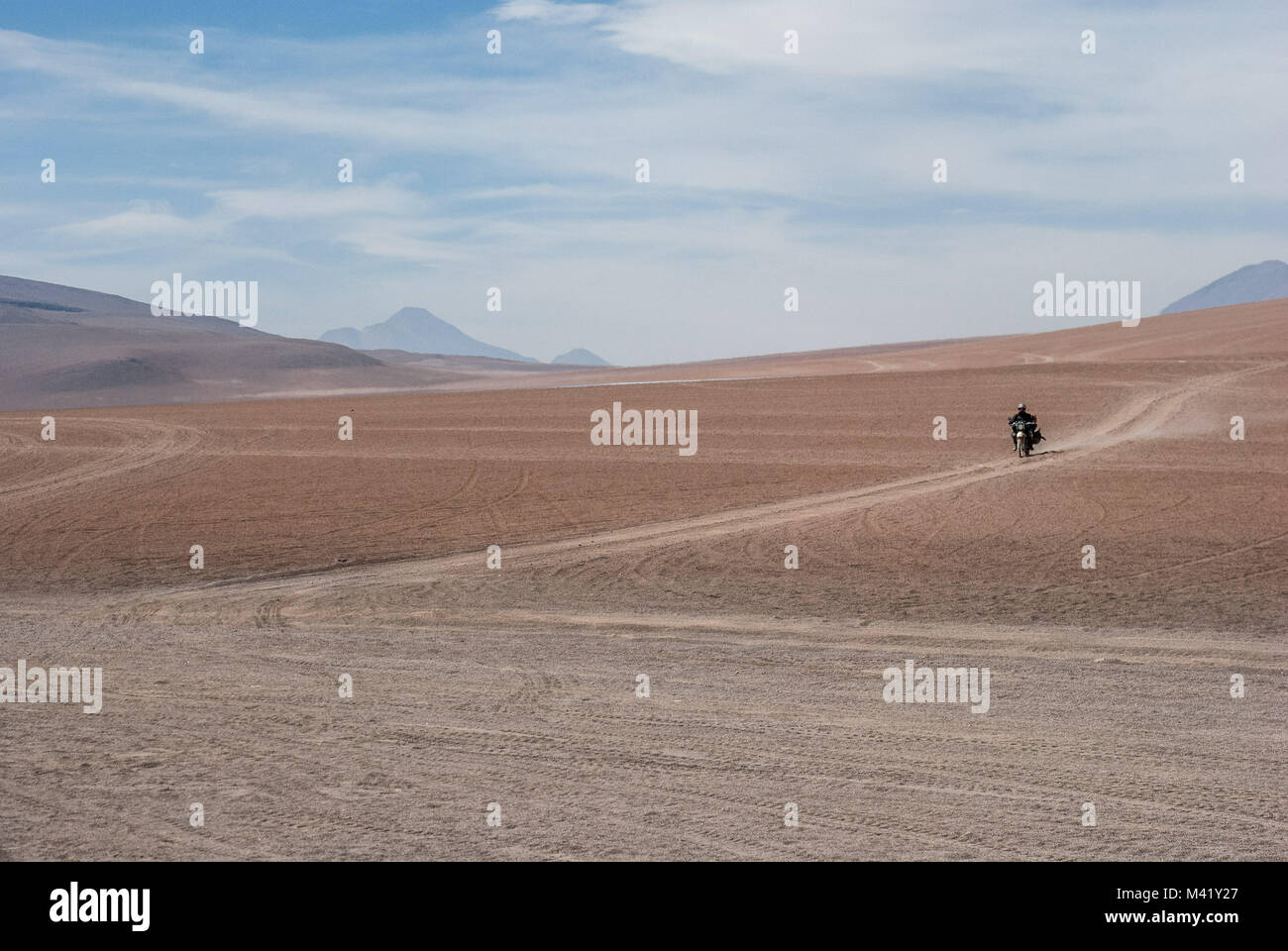 A person riding a motorbike across a deserted sandy landscape in the high plains of the Andes, Bolivia - Stock Image