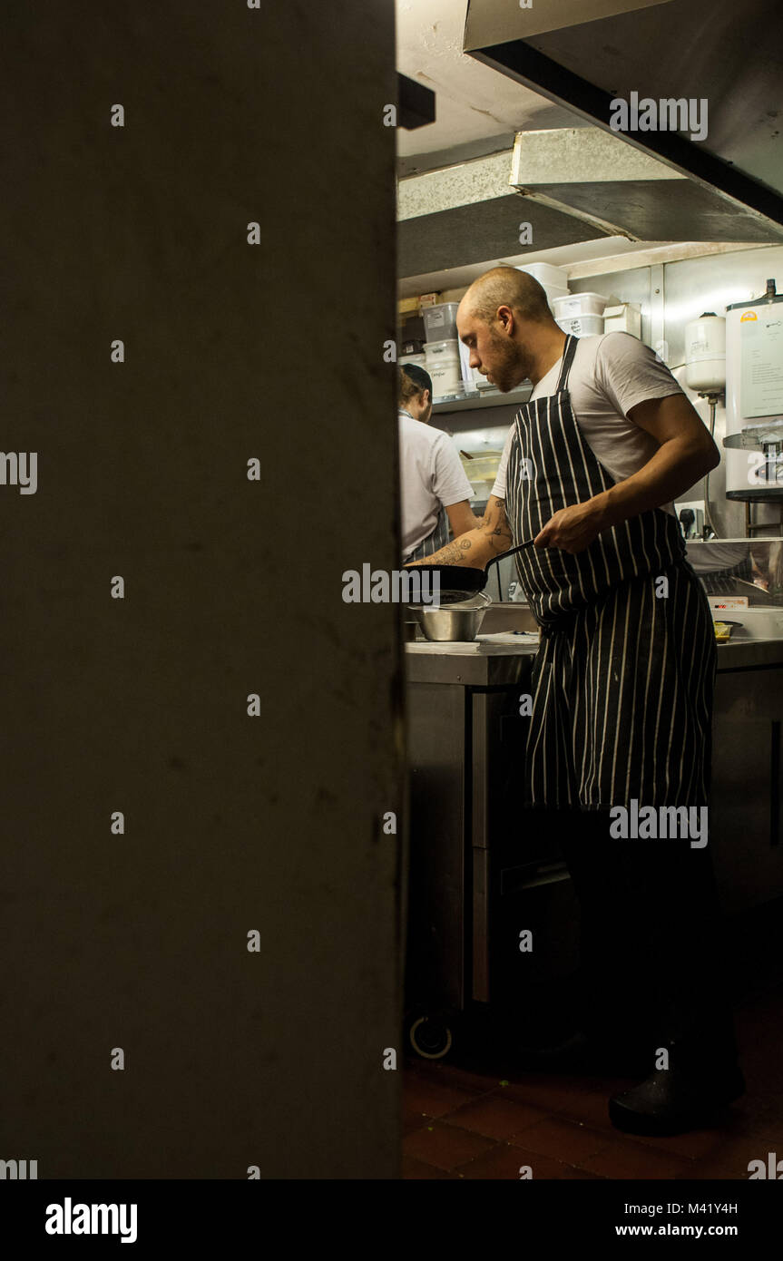 A chef working on his feet in a restaurant kitchen in Bristol, England - Stock Image