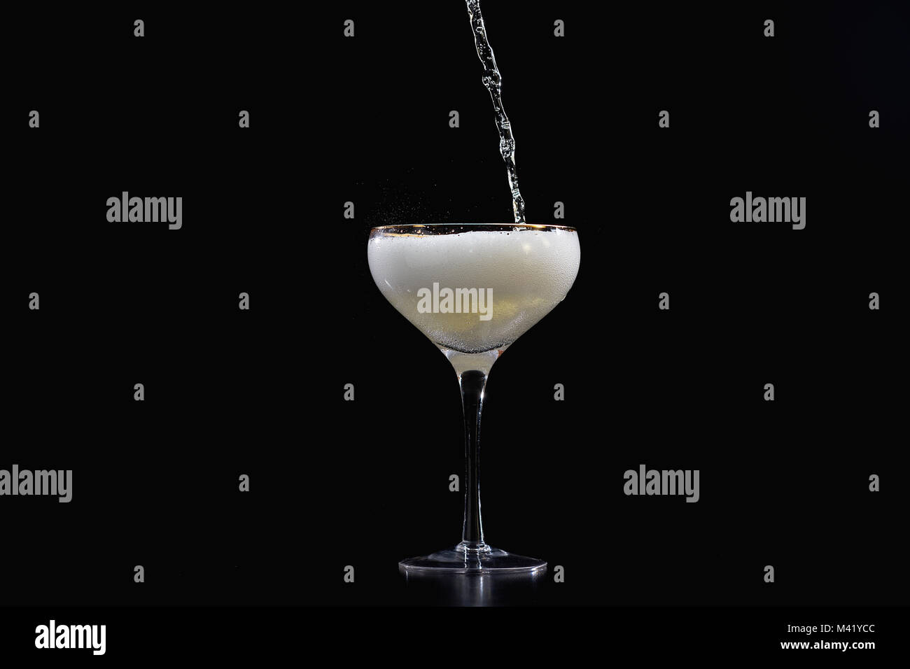 Pouring champagne sparkling wine into glass with black background - Stock Image