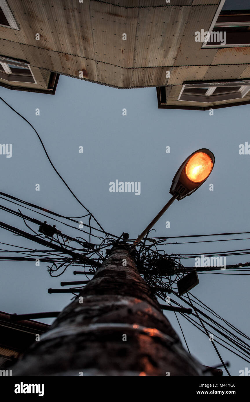 A perspective photo taken from below looking up at a metal sheet house and lamppost - Stock Image