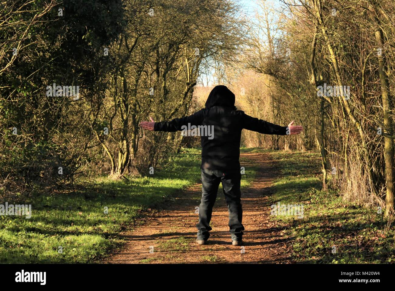 Man wearing hoody with arms outstretched in the countryside on a sunny Winter's day - Stock Image