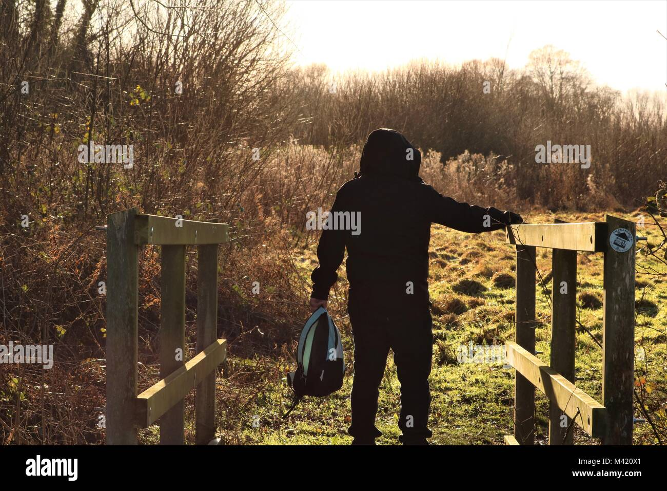Man wearing a hoody holding on to wooden hand rail walking on bridge in the sunshine on a Winter's day - Stock Image