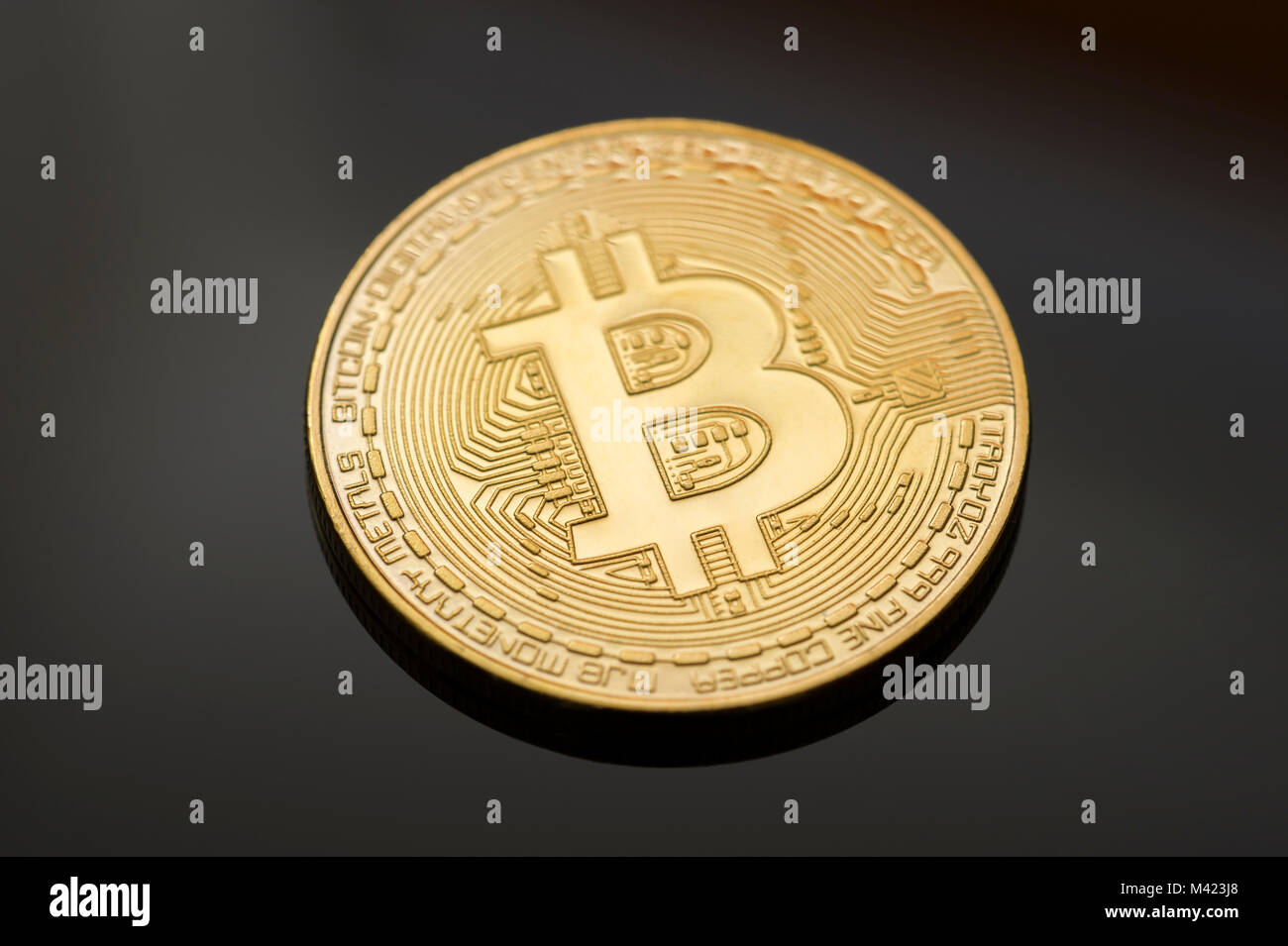 Single gold Bitcoin on black background. One of many digital or cryptocurrencies that uses blockchain technology - Stock Image