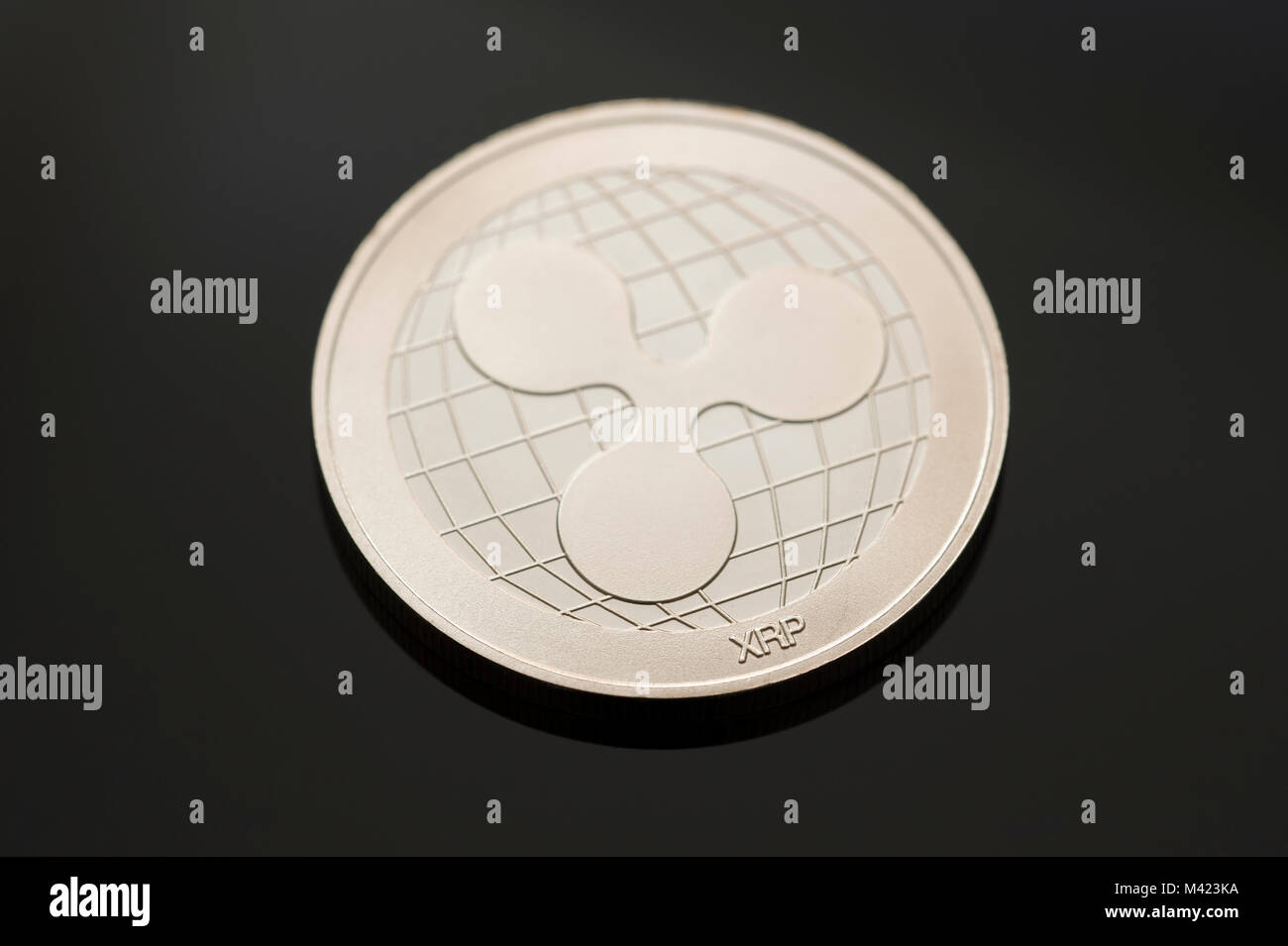 A single Ripple (XRP) token or coin on a black background. One of many digital or cryptocurrencies that use blockchain - Stock Image