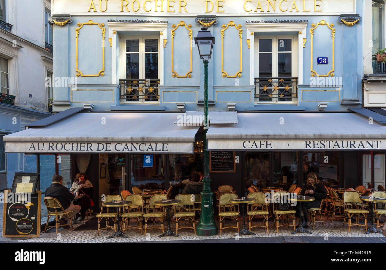 People sitting in a traditional French cafe Au rocher de Cancale on Rue Montorgueil street in Paris, France. - Stock Image