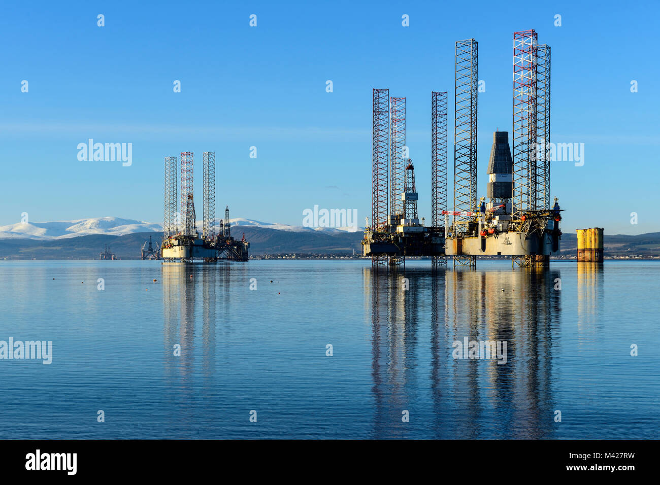 Oil rigs / drilling platforms moored in Cromarty Firth viewed from town of Cromarty on the Black Isle in Ross & Cromarty, Highland Region, Scotland Stock Photo