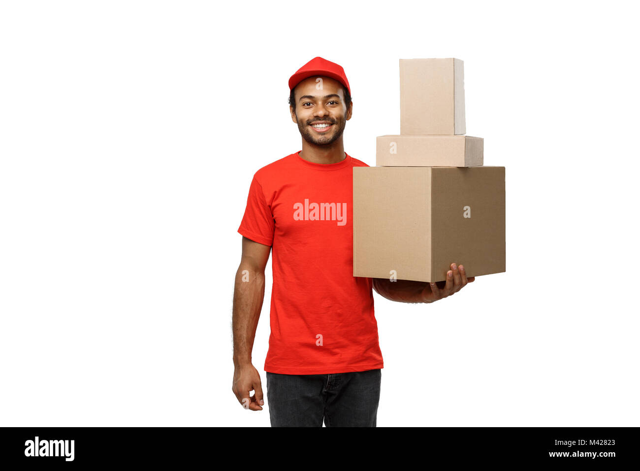 Delivery Concept - Portrait of Happy African American delivery man in red cloth holding a box package. Isolated - Stock Image