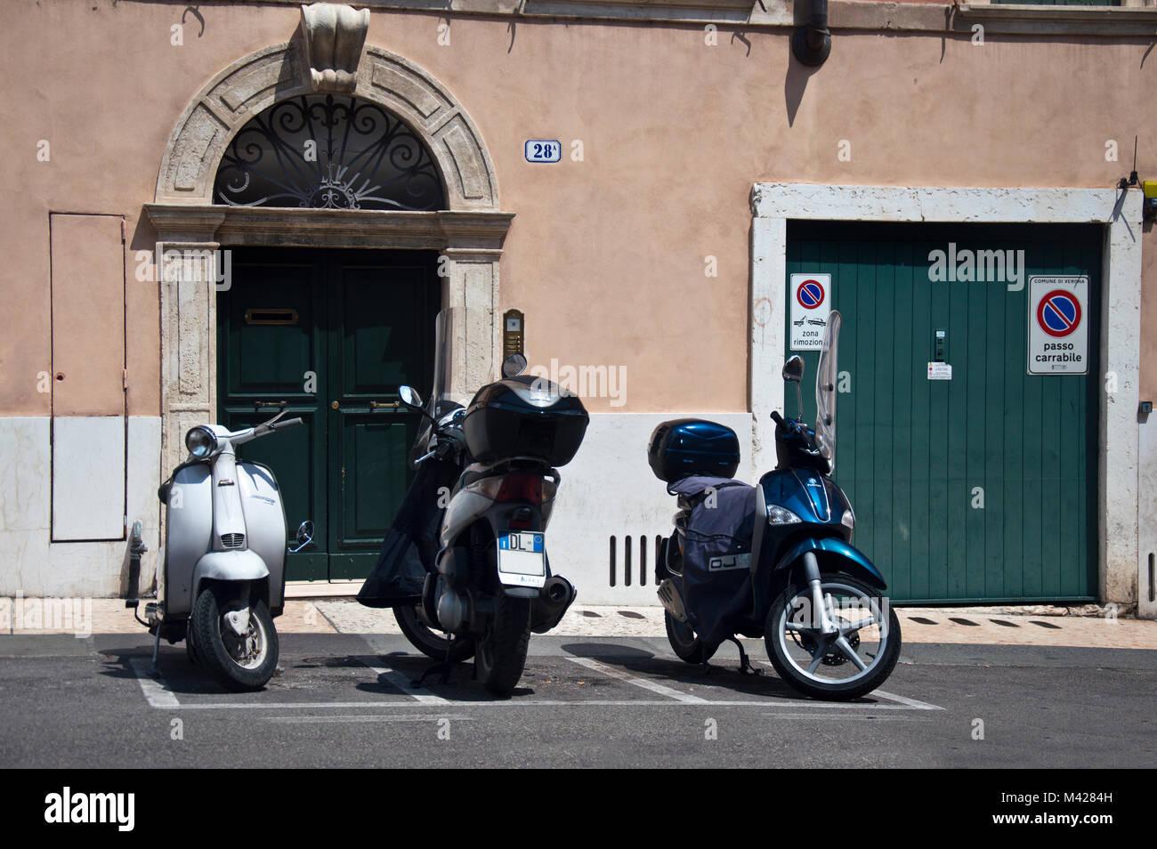 Three motor cycles parked in designated parkinig bays, Verona, Italy - Stock Image