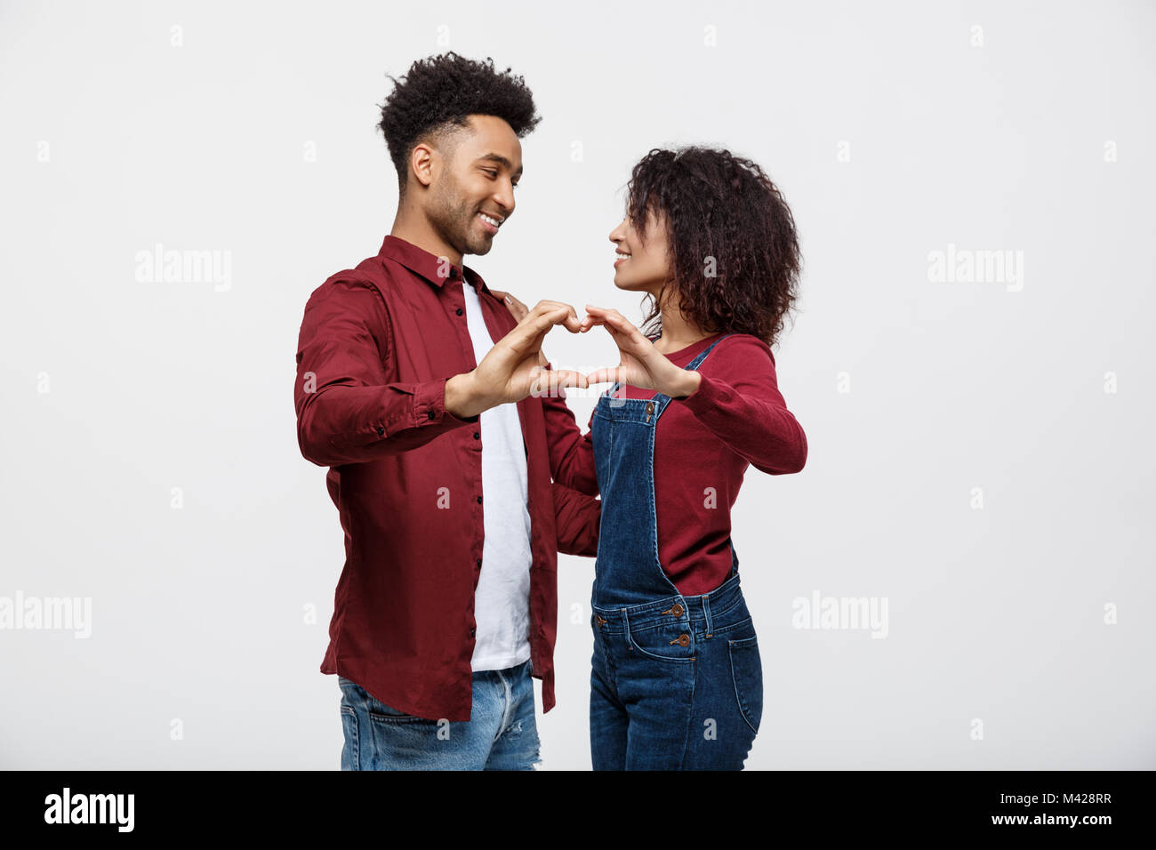 Portrait of a smiling young african couple dressed in casual clothes hugging and showing heart gesture with fingers - Stock Image