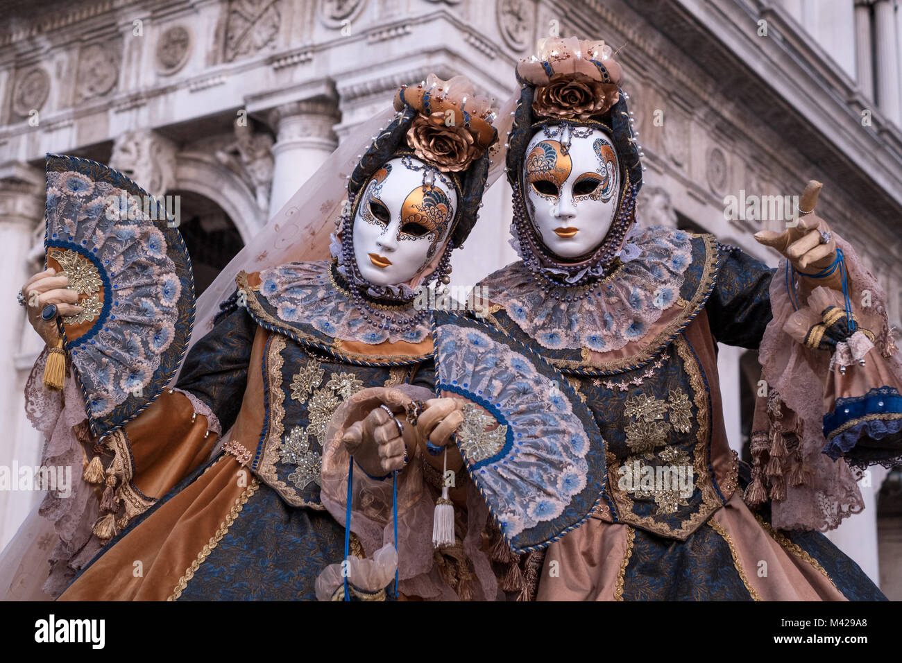 Two women in traditional costumes and masks, with decorated fans, standing in front of the arches at St Marks Square Stock Photo