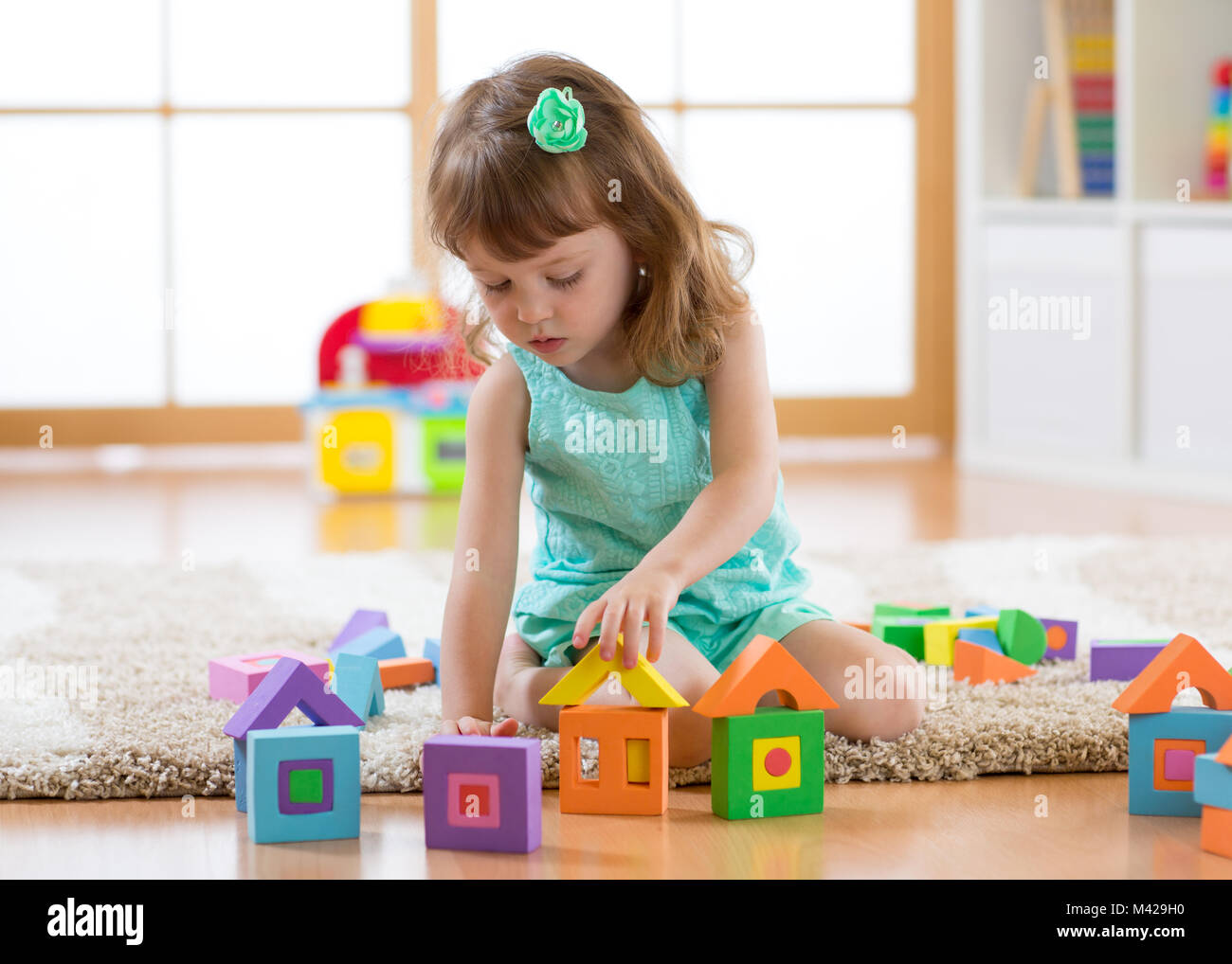 Child girl playing with constructor sitting on the floor - Stock Image