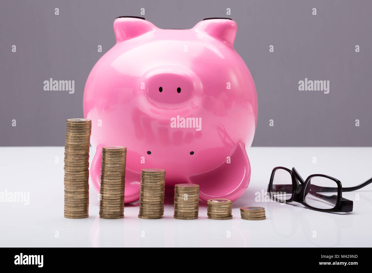 Upside Down Piggy Bank On Table With Eye Glasses And Stacked Coins On Table - Stock Image