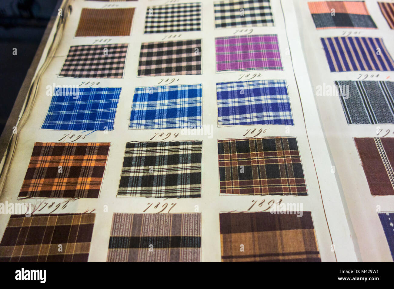 Page in old textile sample book showing chequered fabric samples with different weaving patterns and colour combinations - Stock Image