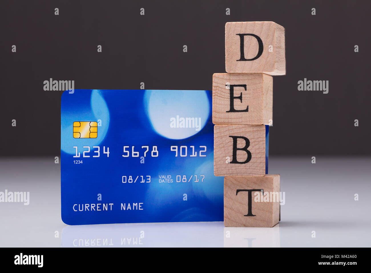 Close-up Of Debt Card And Debt Text On Stacked Wooden Block - Stock Image