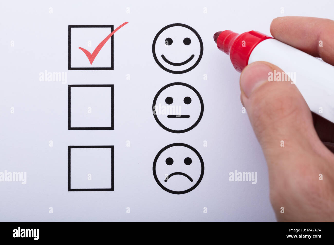 Close-up Of Person's Hand Ticking Off Checked Box With Red Marker - Stock Image