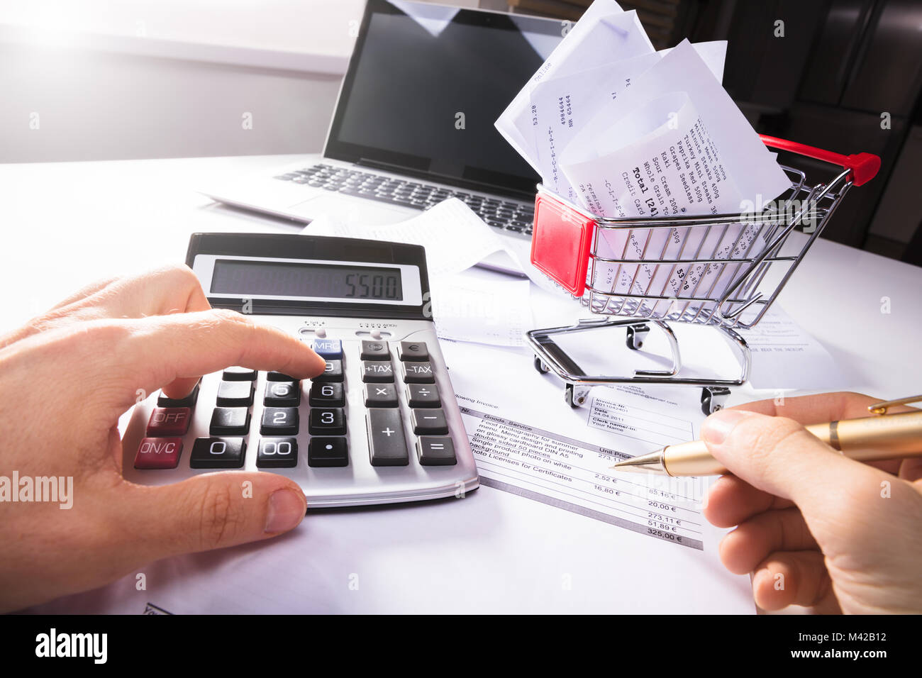 Close-up Of Person Calculating Invoice With Calculator Near Shopping Cart On Desk Stock Photo