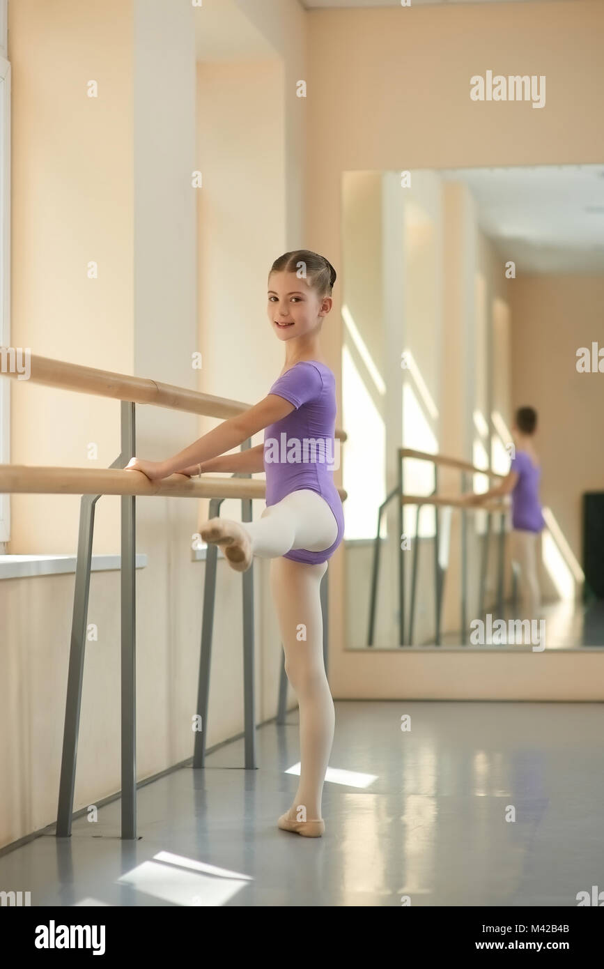 Beautiful young ballerina in ballet studio. Cute young girl training near barre in ballet hall. Ballet leg lift. - Stock Image
