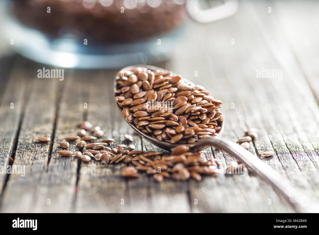 Healthy brown linseed in spoon. - Stock Image