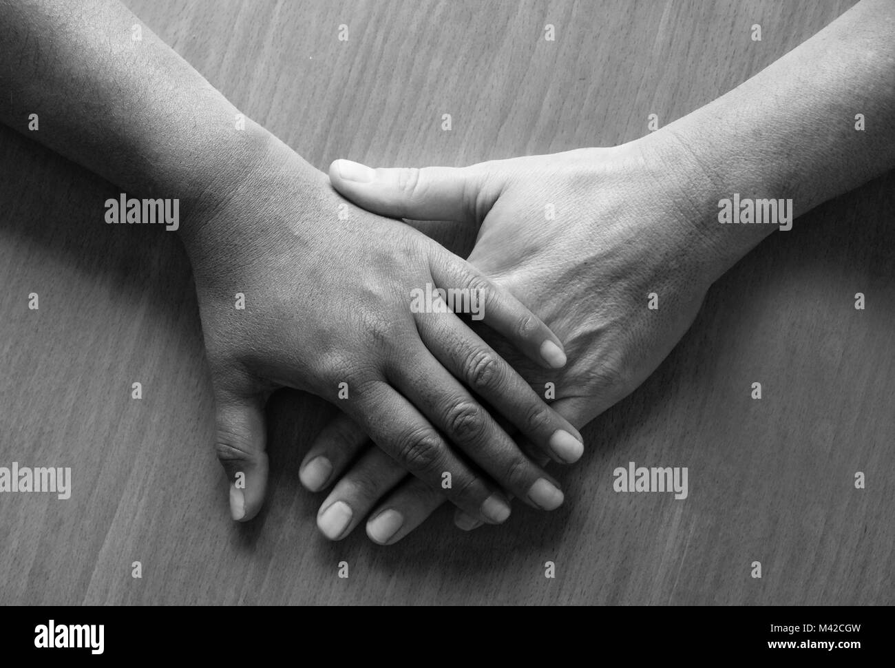 looking down on two fifty year old female hands and lower arms placed ontop of each other, the top hand is Asian - Stock Image