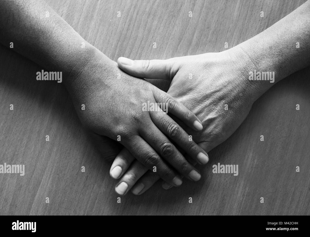 looking down on two fifty year old female hands and lower arms placed ontop of each other, the top hand is Asian Stock Photo
