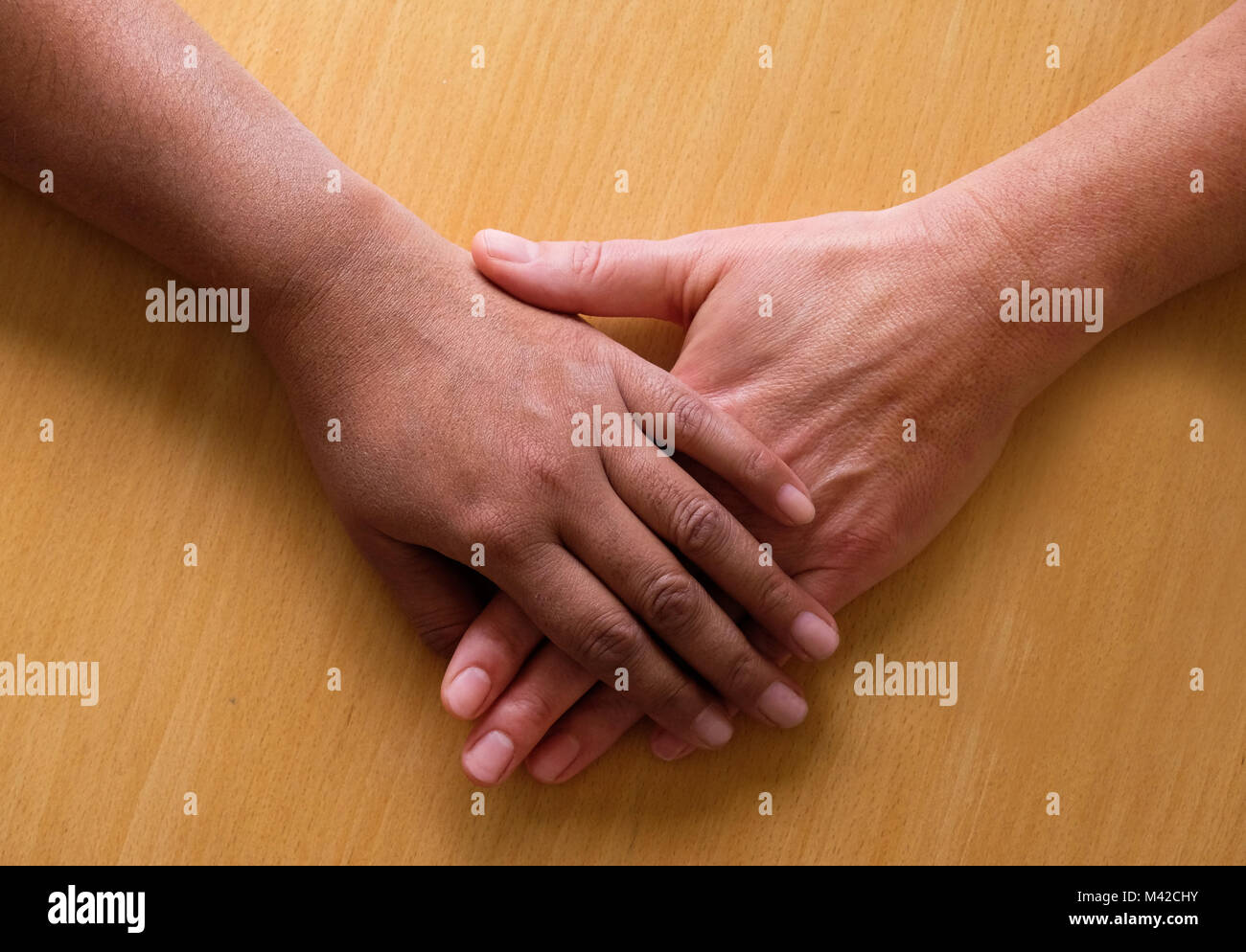 overhead view of two fifty year old female hands and lower arms placed ontop of each other, the top hand is Asian Stock Photo