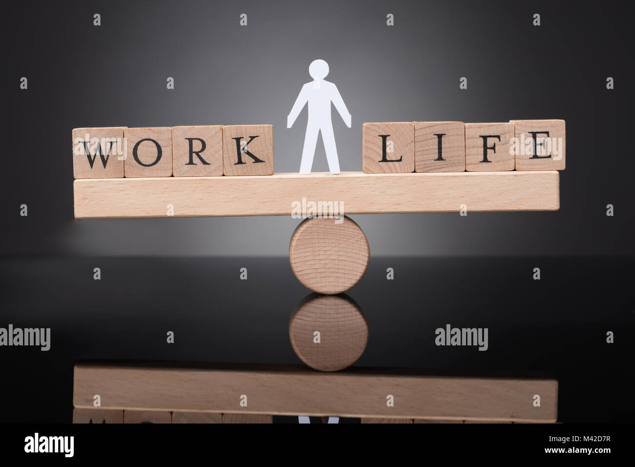 Human Figure Balancing Between Work And Life On Wooden Seesaw Against Black Background - Stock Image