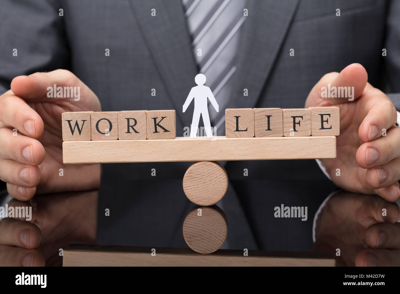 Close-up Of A Businessperson's Hand Protecting Balance Between Life And Work On Wooden Seesaw - Stock Image