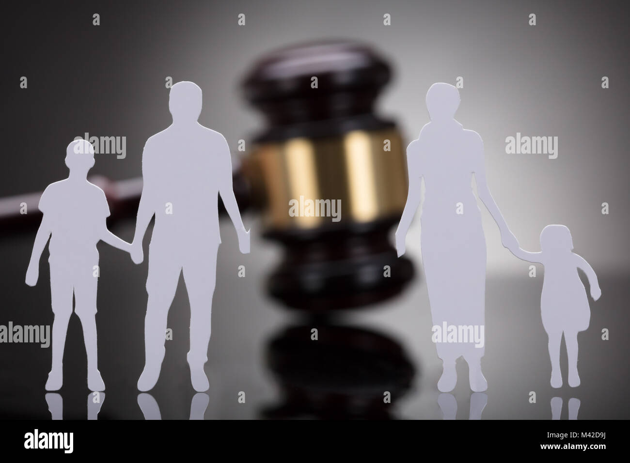 Separation Of Family Figure Cut Out In Front Of Gavel On Grey Background - Stock Image