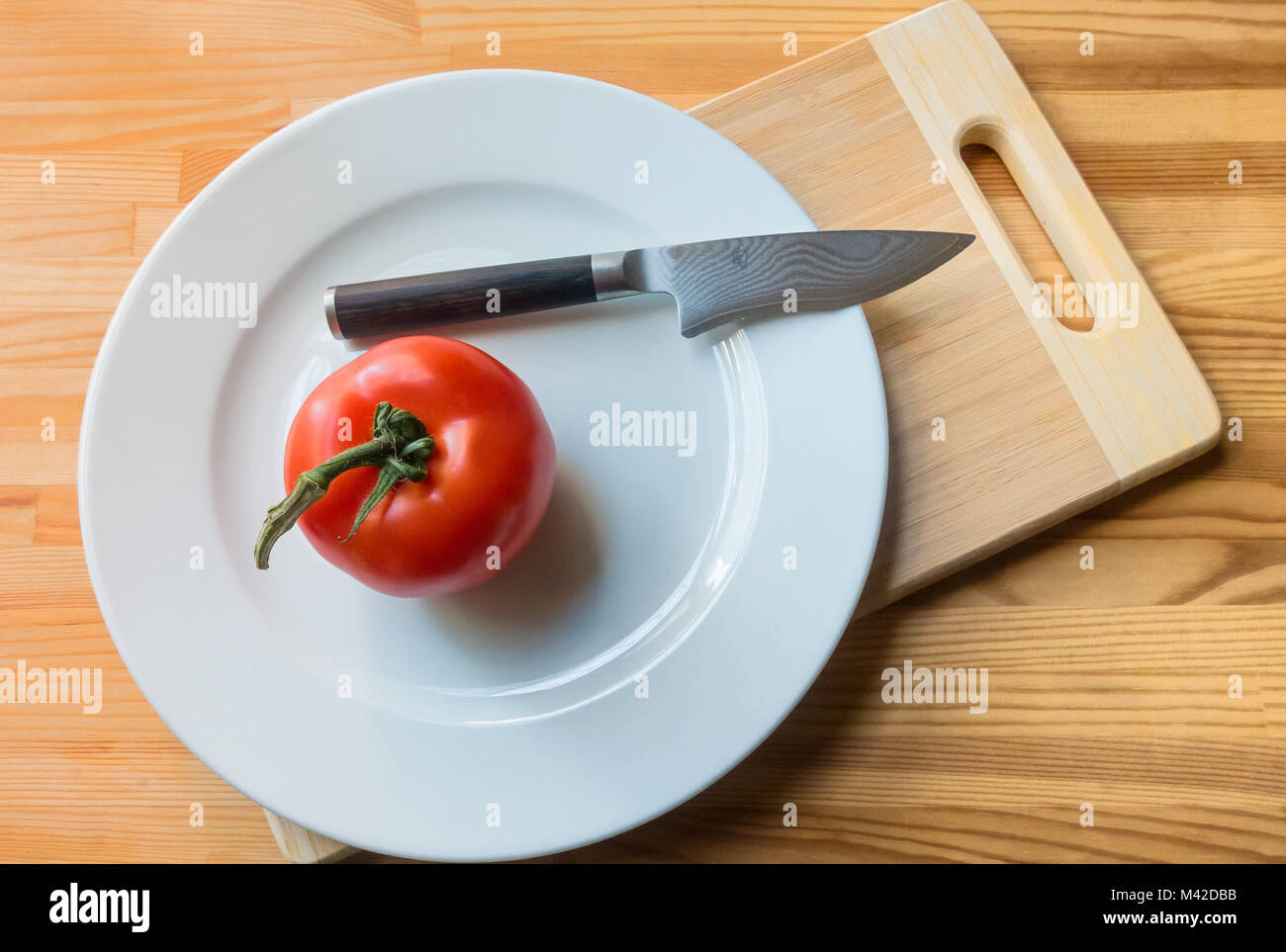 A large vine-ripened tomato on a white plate with knife and cutting board - Stock Image