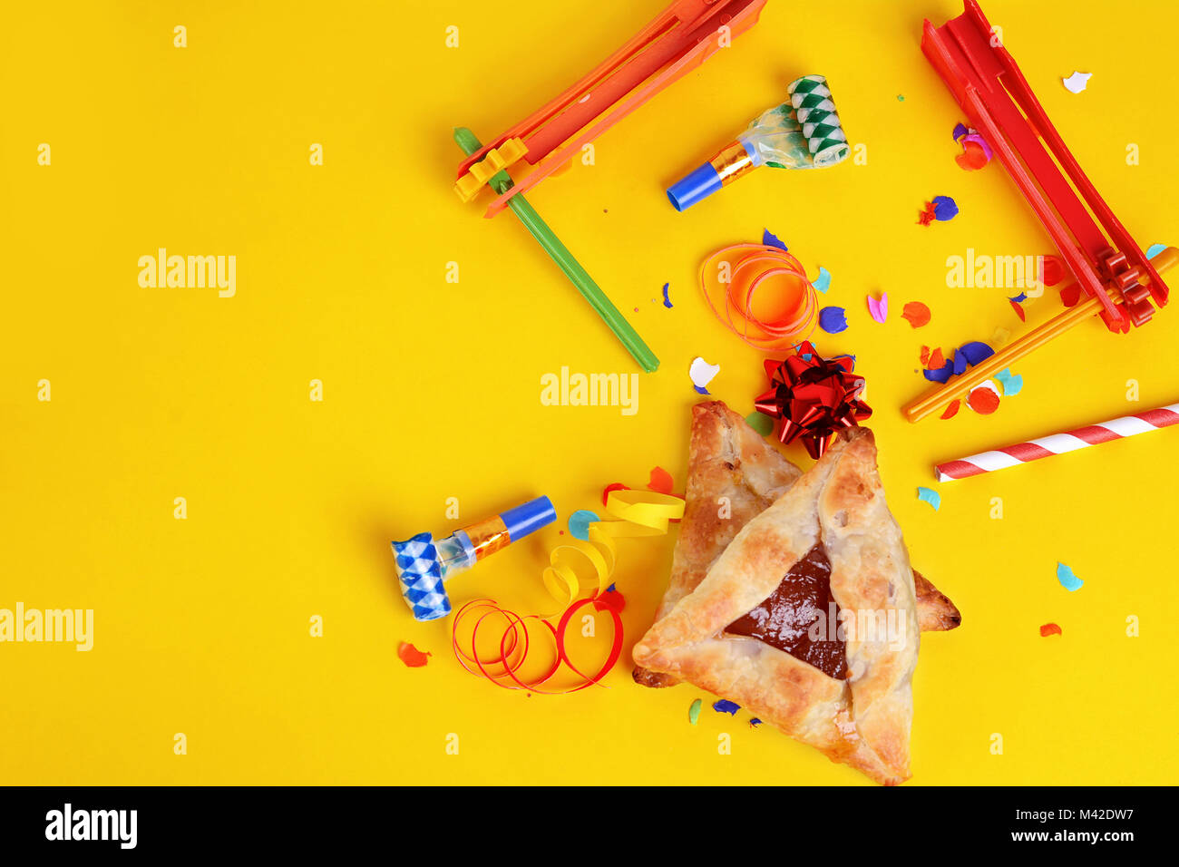 Purim background with party costume and hamantaschen cookies. - Stock Image